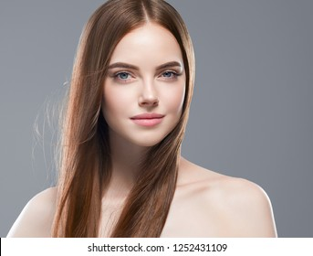 Healthy hair woman with long smooth brunette hair and natural makeup over gray background