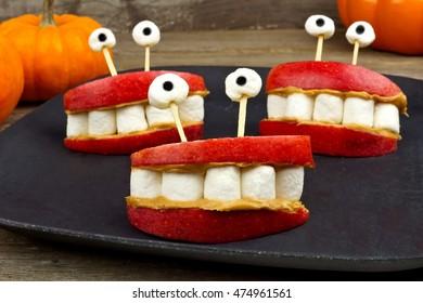 Healthy Halloween apple, marshmallow, peanut butter monster teeth on a black plate