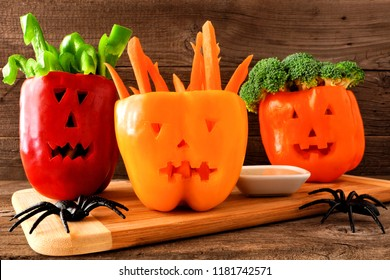 Healthy Halloween food. Vegetables and dip in Jack o Lantern bell peppers. Close up against rustic wood.