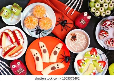 Gesunde Halloween-Obstsnacks. Verschiedene lustige, sprichwörtliche Behandlungen. Tischtennis mit Draufsicht auf schwarzem Hintergrund.