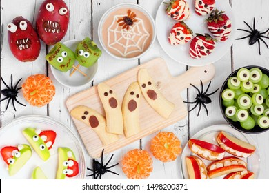 Healthy Halloween fruit snacks. Selection of fun, spooky treats. Top view table scene over a white wood background.