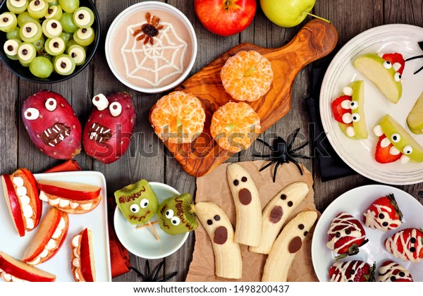 Healthy Halloween fruit snacks. Selection of fun, spooky treats. Top view table scene over a rustic wood background.