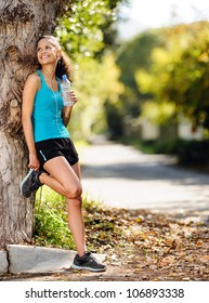 healthy happy fitness woman resting in suburb with water bottle after workout exercise session. vitality lifestyle runner. panorama with copyspace