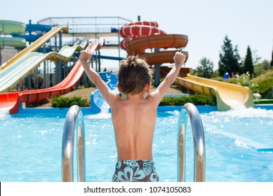 healthy happy little kid near blue swimming pool in water park with water tube slides in summer
