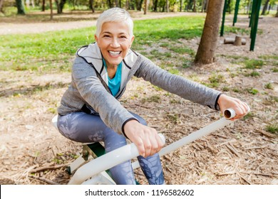 Healthy Happy Mature Woman Practicing At Outdoor Gym, Sports Clothes, Sporty Elderly Female With Short Hair, Workout Training.