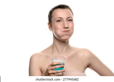 Healthy happy woman rinsing and gargling while using mouthwash from a glass, during daily oral hygiene routine, portrait with bare shoulders, with copy space, isolated on white