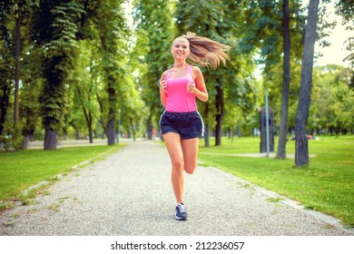healthy and happy woman running in urban park with headphones and music