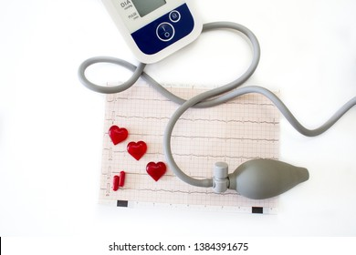 Healthy heart concept: cardiogram, tonometer, red hearts and pills on white background