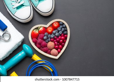Healthy heart  diet and sport gym equipment concept on blackboard