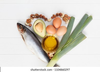 Healthy heart food with fish, avocado, eggs, leek, olive oil, nut on white wooden kitchen table or background. Top view. High in omega 3. Super food high vitamin D and dietary fiber for healthy food.
