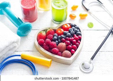 Healthy heart stethoscope diet and sport gym equipment concept on white background