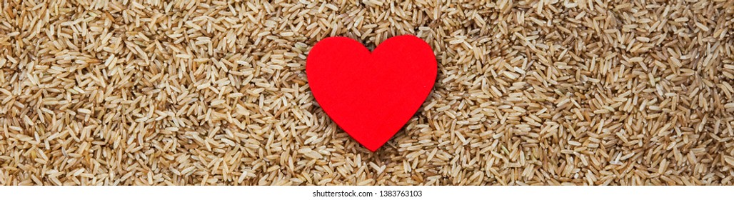Healthy heart and wholemeal rice - food concept for loving rice, a healthy diet, dieting, lifestyle & nutrition: panorama / banner with lots of design space.