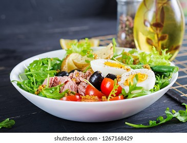 Healthy hearty salad of tuna, green beans, tomatoes, eggs, potatoes, black olives close-up in a bowl on the table. Salad Nicoise. French cuisine.