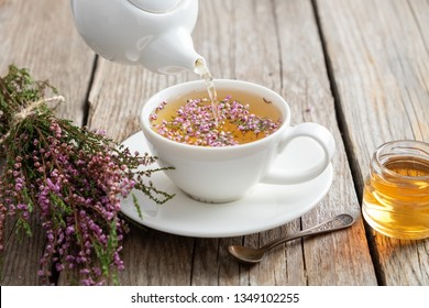 Healthy heather tea poured into white cup. Teapot, small honey jar and heather bunch.