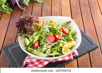 Healthy herb salad on wood table background with red square napkin.