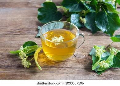 Healthy herbal linden tea with bunch of fresh linden flowers on wooden background. Cup of organic linden tea, herbal drink.