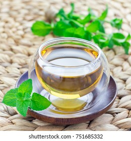 Healthy herbal mint tea in oriental glass cup with fresh peppermint on background, square format