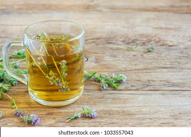 Healthy herbal tea with bunch of fresh wild thyme on old wooden background. Cup of thyme tea, herbal drink.