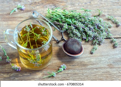 Healthy herbal tea with bunch of fresh wild thyme and vintage tea-strainer on old wooden background. Cup of thyme tea, herbal drink.