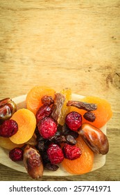 Healthy high fiber food, organic nutrition. Closeup different varieties mix of dried fruits on wooden spoon.