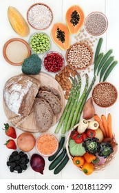 Healthy high fibre food concept with fruit, vegetables, whole grain rye bread, legumes, grains and cereals on rustic white wood background. High in antioxidants, anthocyanins, vitamins and minerals.