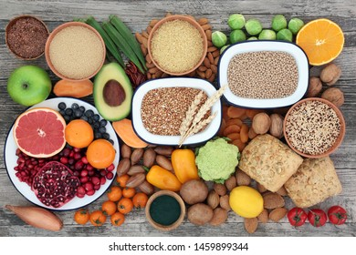 Healthy high fibre food concept with fruit, vegetables, grains, nuts, seeds, seeded wholegrain rolls & spirulina powder. Foods with antioxidants, anthocyanins, vitamins & minerals. Top view.