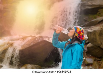 Healthy hiker girl drinking water in nature hike. Beautiful young woman hiking happy with a water bottle in front of a waterfall. back view.