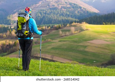 Healthy hiker girl in nature hike. Beautiful young woman hiking happy with Trekking pole stands on a meadow. Background beautiful mountayns and blue sky with clouds