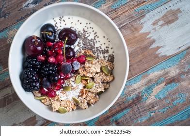 Gesundes hausgemachtes Haferbrei mit Kefir-Jogurt und mit Brombeeren, Kirschen, Granatapfelsen, Kürbis und Chiasamen überzogen. Auf einem rustikalen Holztisch serviert.