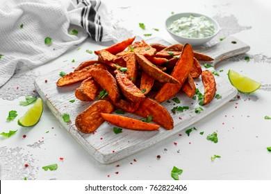 Healthy Homemade Baked Orange Sweet Potato wedges with fresh cream dip sauce, herbs, salt and pepper.