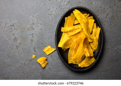 Healthy Homemade banana Plantain Chips on black plate, slate background.
