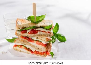 Healthy homemade caprese sandwich with tomato, mozzarella and basil, selective focus