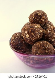 Healthy homemade chocolate truffles in a purple glass bowl