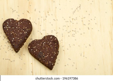 Healthy homemade dark chocolate chia seed love heart cookies on a wooden background