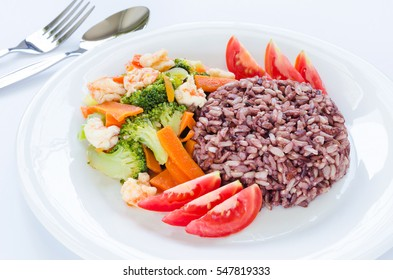 Healthy homemade dish with brown & red rice, stir-fried shrimp carrot broccoli and fresh sliced tomato on white plate with silver fork and spoon on white background for good health