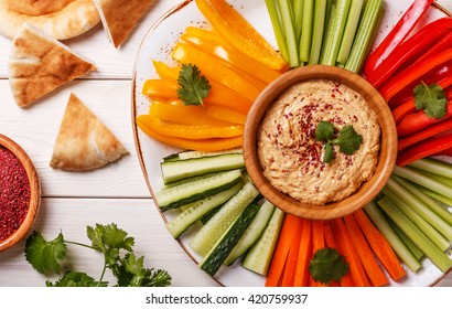 Healthy homemade hummus with assorted fresh vegetables and pita bread.