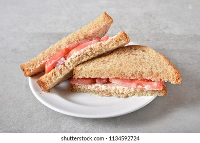 A healthy homemade tomato sandwich on whole wheat bread.