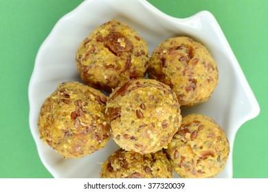 Healthy Honey Peanut Butter Date Walnut Protein Balls on Green Background