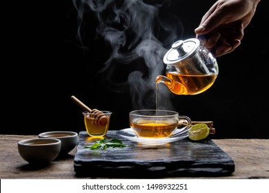 Healthy hot tea with hot steam, honey water and a cup of beautifully placed tea. - Healthy herbal water concept