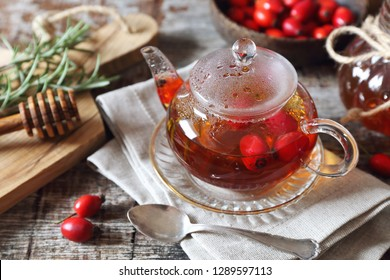 Healthy hot winter beverage. Rose hip tea in teapot, rosemary and berries