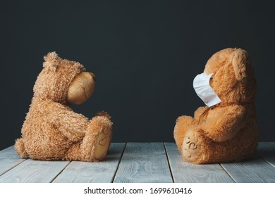 healthy and ill teddy bears sitting on distance at each other