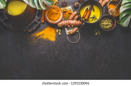 Healthy ingredients border for making turmeric milk drink with fresh turmeric roots , spices and honey on dark background. Hot winter beverage. Immune boosting remedy , detox and dieting concept .