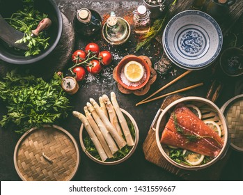 Healthy ingredients for low carb meal cooking: salmon in asian bamboo steamer , asparagus bunch, fresh herbs and oil and sauce bottles on dark table background, top view. Asian cuisine. Keto diet