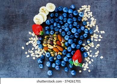 Healthy ingredients (oat flakes, berries with yogurt and seeds) for breakfast or smoothie on dark vintage background - Healthy food, Diet, Detox, Clean Eating or Vegetarian concept.