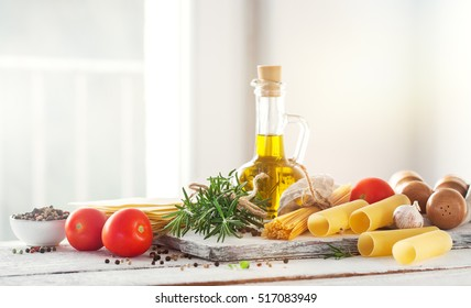 Healthy ingredients on a kitchen table - spaghetti, olive oil, tomatoes, spices and fresh italian herbs on a shiny background. Cooking or healthy life concept, horizontal