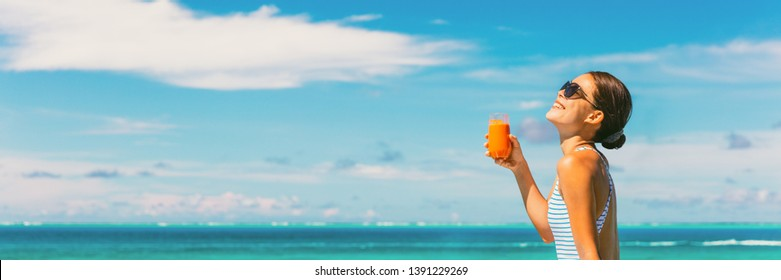 Healthy juice detox happy woman drinking carrot juicing smoothie glass on summer sunny day vacation background banner panorama. Copy space on blue sky.
