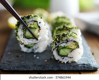 healthy kale and avocado sushi roll with chopsticks
