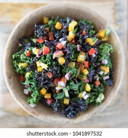 Healthy kale salad with fresh bell peppers and red onions in a wooden bowl viewed from above.