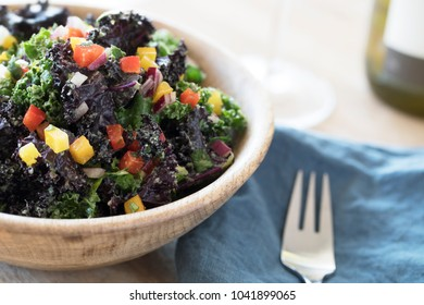 Healthy kale salad with fresh bell peppers and red onions in a wooden bowl.