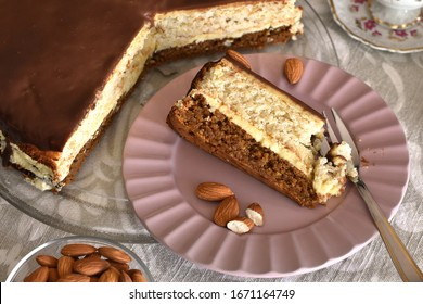 Healthy keto layered cake or dessert slice, brown part of walnuts and white of almonds filled with cashew nuts cream, served on pink plate